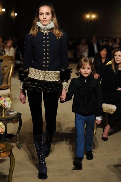 A model walking at the show with Hudson Kroenig, Brad Kroenig's son.