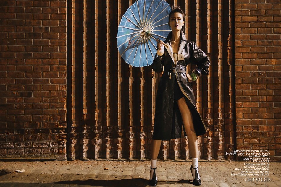 """Power Geisha"" Photography by Guillaume Guadet for The Untitled Magazine. Leather trench coat by Celine. Snakeskin cream bra with gold buckle by Zana Bayne. Black snakeskin belt by Zana Bayne. Costume bracelets by Kenneth Jay Lane. Black shorts by Houghton. White socks by Ozone. Black T-Strap pumps by Celine."